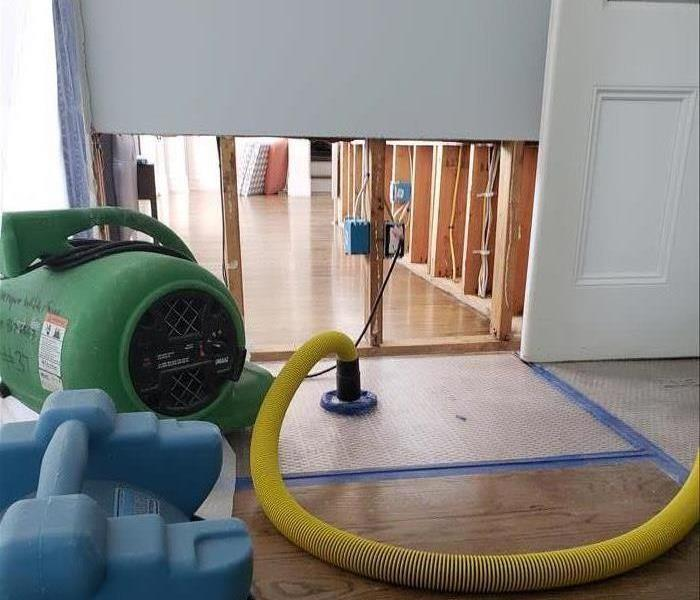 Floor mat drying system set up on wood floor next to a stud wall.
