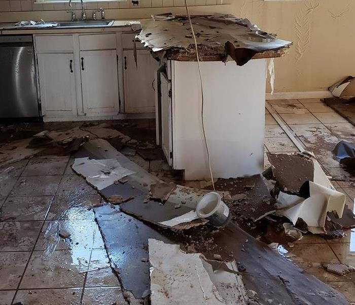 Kitchen counter and tile floor with damaged ceiling pieces on top of it.