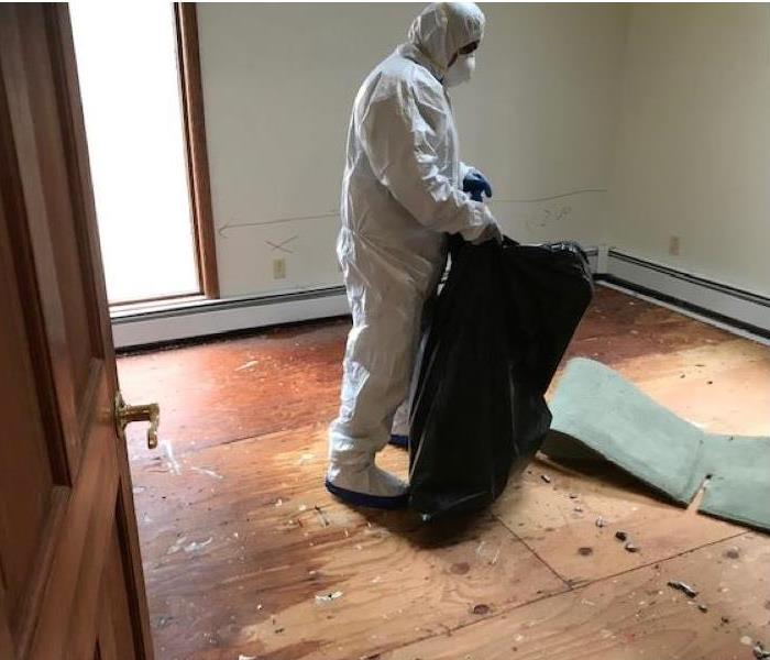 A technician in a PPE suit bagging up carpet.